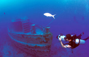 A diver photographs Joe's Tug, which lies eerily intact on the bottom.