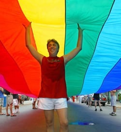 Gilbert Baker savors the moment as his 1.25-mile rainbow flag is unfurled down Key West's Duval Street. (Photo by Mike Hollar, Florida Keys News Bureau)