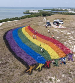 "Key West landscape ""artists"" put finishing touches on a giant rainbow flag atop ""Mount Trashmore."" (Photo by Andy Newman/Florida Keys News Bureau)"