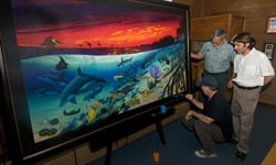 """World-renowned marine life artist Wyland (front) signs his painting """"Marine Sanctuary: Mangroves to the Sea,"""" created for the Pennekamp birthday. (Photo by Andy Newman, Florida Keys News Bureau)"""