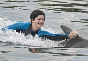 U.S. Army medic Rachael Rodgers who had her left leg amputated below the knee after being bitten by a brown recluse spider, gets a dorsal tow courtesy of Tursi the dolphin at Dolphin Research Center in Marathon.