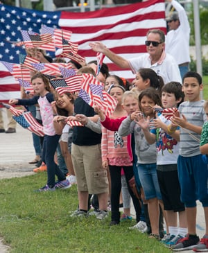 Elementary school students and their teachers greet injured military personnel as they travel down the Florida Keys Overseas Highway.
