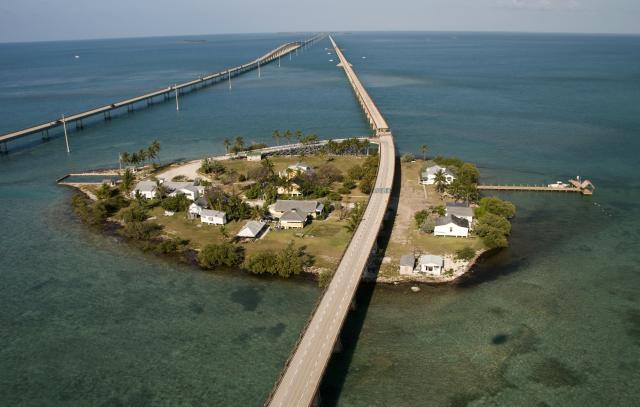 Iconic Pigeon Key is a small historic island beneath the Old Seven Mile Bridge that housed workers constructing the Florida Keys Over-Sea Railroad in the early 1900s.