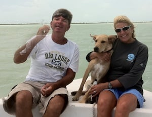 Bobby, Andrea and puppy Clark on the water.