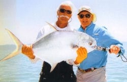 Fishing guide Chris Robinson (left) and his angler display a permit caught in Keys waters.