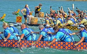 Teams of 20 paddlers power their sleek 40-foot-long boats in unison, racing parallel to the shore.