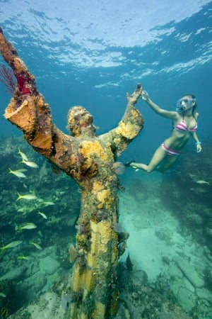 Since the 8.6-foot sculpture was placed in 1965, its outstretched arms have reached upward from its pedestal, rising so close to the surface that both divers and snorkelers can view the watery effigy with ease. Images: Stephen Frink
