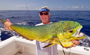 "Johnson displays a nice dolphin fish he caught while trolling in his ""Three Rings"" center console fishing boat off Islamorada."