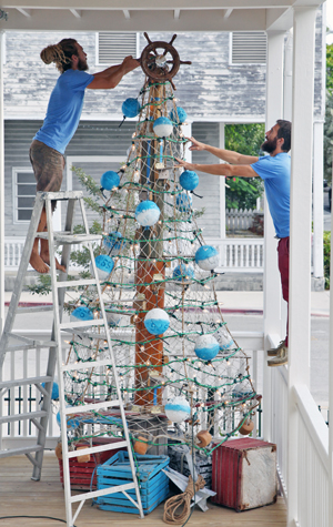 Troy Roberts (left) places a ships wheel at the top of the MerryTime maritime Christmas tree, created by COAST Founder and Creative Director Billy Kearins (right). The approximately 12x8 foot construction, is made entirely of re-purposed, recycled materials, including trap floats, netting, lobster traps, a portion of the mastof a historic wooden sail boat, and other maritime objects. Image: Carol Tedesco