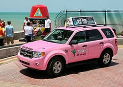 A new Five Sixes Taxi hybrid vehicle rolls past the Southernmost Point marker Wednesda in Key West, Fla. (Photos by Rob O'Neal/Florida Keys News Bureau)