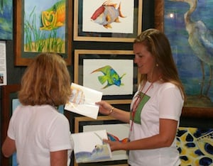 Lowe (right) shares her giclee prints with an art show patron at the Pigeon Key Art Festival, during February in Marathon.