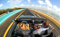 "Amy Pierson, left, and Ken Mausolf drive on the new ""18-mile Stretch"" near Key Largo, Fla.,  that connects the Florida Keys to the South Florida mainland. The barrier's Belize blue color was chosen by marine artist Wyland to match Florida Keys' waters and skies. Photo by Andy Newman/Florida Keys News Bureau"