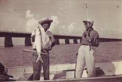 In an undated photo, angler and guide show off a tournament bonefish, with the historic Old Seven Mile Bridge in the background. Today, catch-and-release is a standard fishing practice.